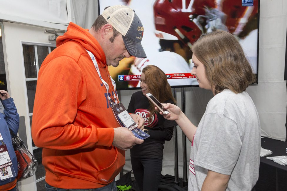 Event staff checking in attendees with smart phone
